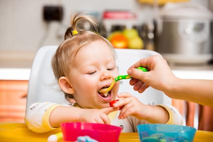 Child girl eats porridge from a spoon on kitchen.